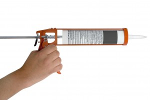 hand with caulk gun